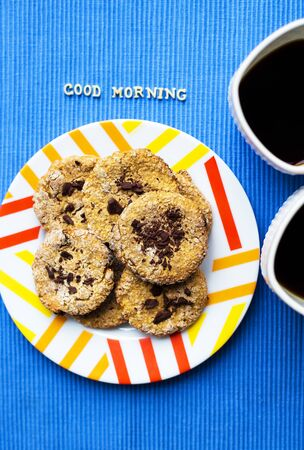 Oatmeal cookies with chocolate on blue napkin and two cups of coffee, good morning inscription