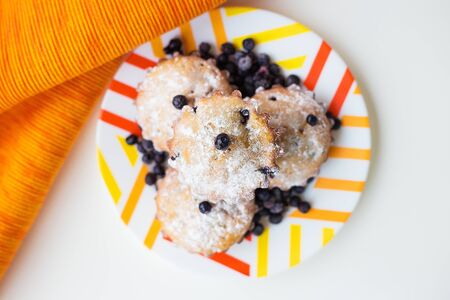Blueberry muffins on a napkin and bright orange plate, close-up