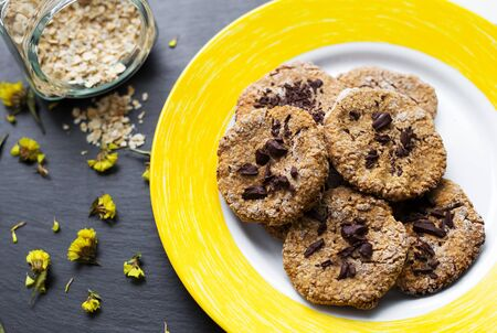 Oatmeal cookies with chocolate on a yellow plate 免版税图像