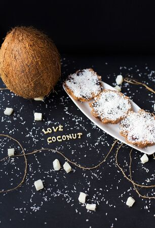coconut muffins on a black background with words like candied fruits and coconuts Stok Fotoğraf