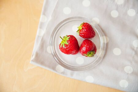 strawberries in a glass bowl on a wooden background and a beige napkin peas Фото со стока - 131871469