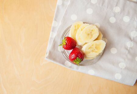 strawberry and banana on a glass plate on a wooden background
