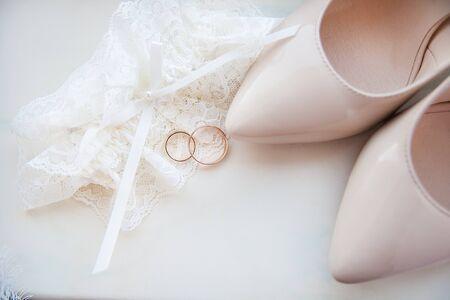 Beautiful brides wedding shoes, garter and wedding rings 写真素材