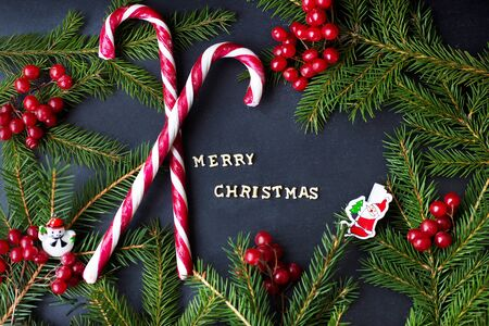 Candy on black background with branches of trees. The inscription Merry Christmas. Stockfoto