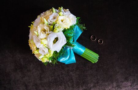 Wedding bouquet with rings lying on the sofa