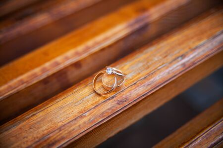 three gold wedding rings on a wooden bench