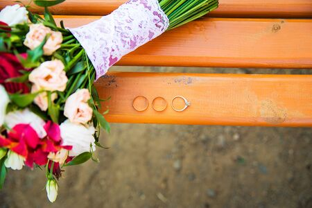 Wedding rings beautiful delicate bouquet, lying on a swing in the park