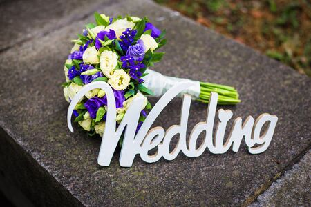 Word wedding and bridal bouquet lying on the pavement
