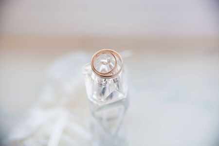 beautiful gold rings lie on a jar of perfume Stock Photo