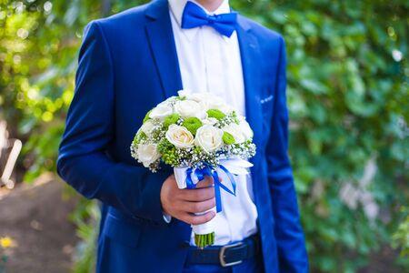 Beautiful wedding bouquet in hands of the groom