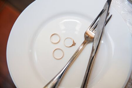 Tableware, a beautiful golden wedding ring on a white plate