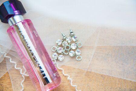 perfume jar and silver earrings bride closeup
