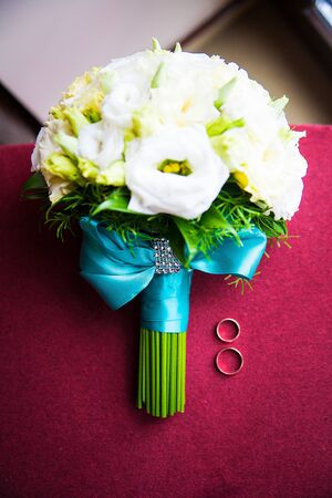 Wedding bouquet with rings lying on the sofa Stock Photo