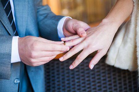 groom wears a ring on a finger of his beloved Banco de Imagens