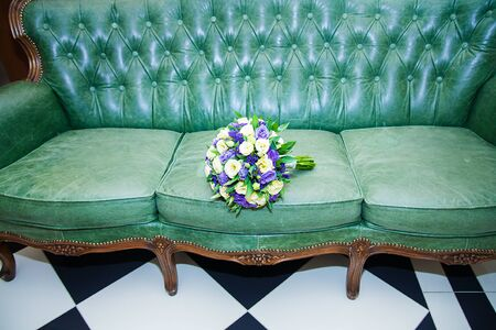 Close-up of beautifully arranged wedding bouquet on leather sofa