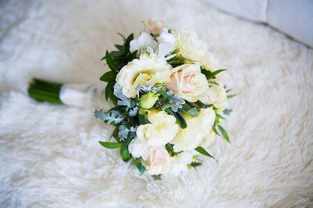 Close-up of beautifully arranged wedding bouquet on sofa