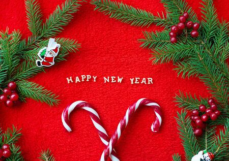 Christmas tree and candy on a red background with the words Happy New Year Postcard. Banco de Imagens - 132237874