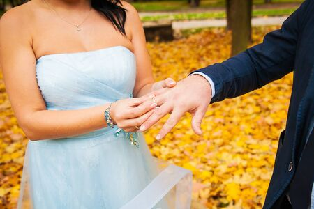 groom's hand putting a wedding ring on the bride's finger Banque d'images - 131958284