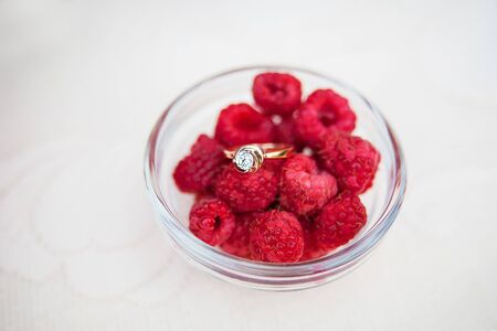 Wedding rings in a bowl with raspberries top view