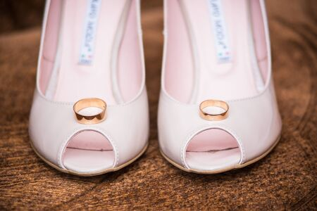 rings lie in the shoes of the bride close-up shot