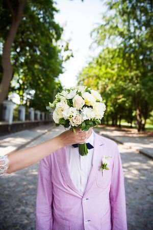 the bride holding a bouquet in the face of the groom Stock Photo