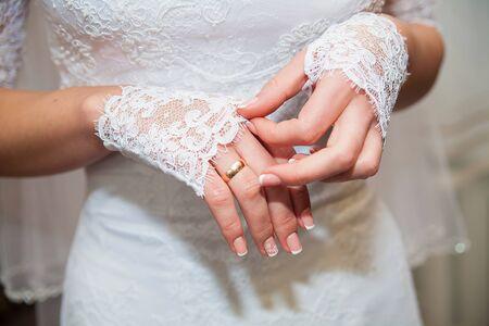 Manos de la hermosa novia en primer plano de guantes blancos
