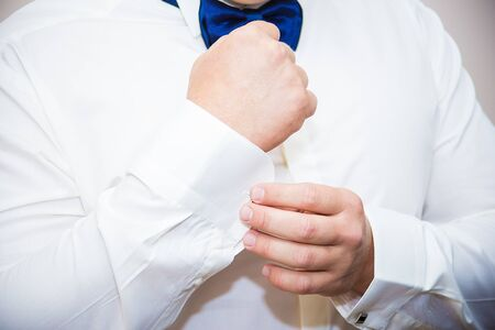 Groom buttons cuffs on his white shirt