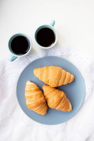 two cups of coffee with croissants on the background of laces on a white background