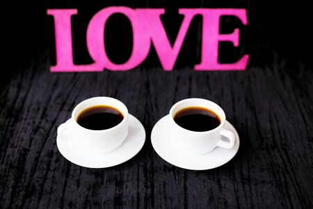 two cups of coffee on pink background inscription love. Фото со стока