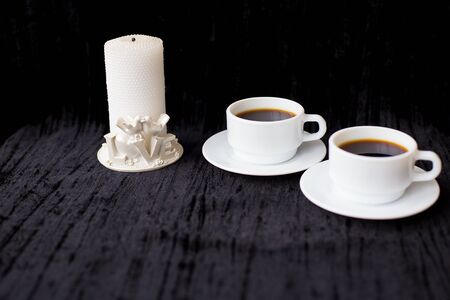 candle and two cups of coffee on a black background. Banco de Imagens