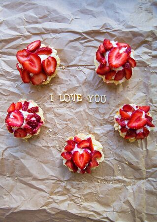 Bright cupcake with strawberries lies on craft paper, the inscription I love you. valentine card