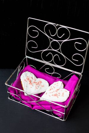 Cookies in the form of heart lies in a casket with pink cloth. valentine card Banco de Imagens