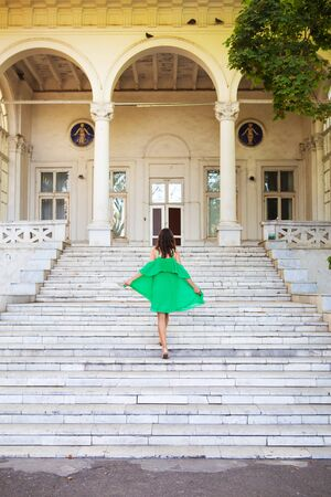 Summer vacation. A girl in a green dress stands on the stairs near the sanatorium. Chkalov in Odessa. Stock Photo