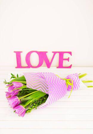 bouquet of purple tulips on white table, wooden letters love. Reklamní fotografie