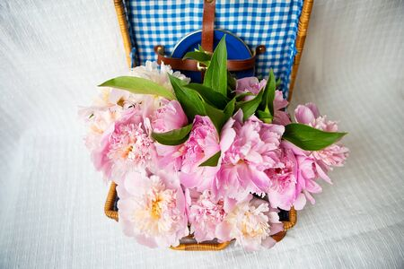 The beauty of a pink peonies bouquet in a vintage authentic brown suitcase, closeup. Beautiful composition.