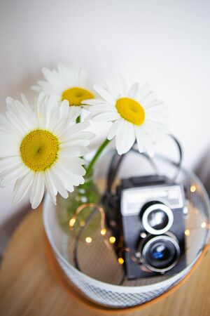 Old vintage rustic camera with a bouquet of daisy flowers on a wooden board. Close-up, bokeh.