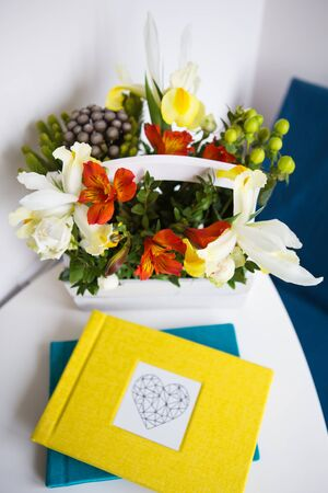 Very beautiful wooden white basket with different colors. Yellow album. Close-up.