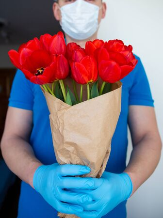 Contactless delivery in a mask and disposable gloves of a bouquet of beautiful red tulips, the concept of quarantine and isolation during the coronavirus pandemic