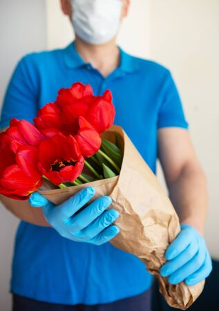 Contactless flower delivery by courier in a protective mask, medical gloves with a bouquet of red tulips. Close-up. Фото со стока