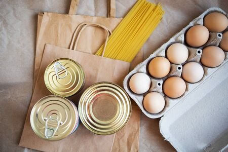Eggs, canned food, pasta, products in environmentally friendly craft packages. Vegetarian healthy organic foods from the market. Donation, help for those in need. Archivio Fotografico - 149593276