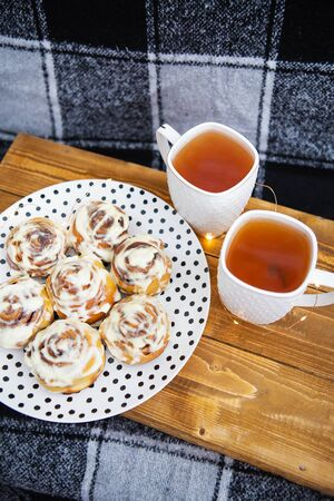 Two cups of black tea stand on a wooden tray on the sofa with a black and white checkered plaid. Fresh and fragrant cinnamon rolls close up lie on a plate with polka dots, beautiful morning.
