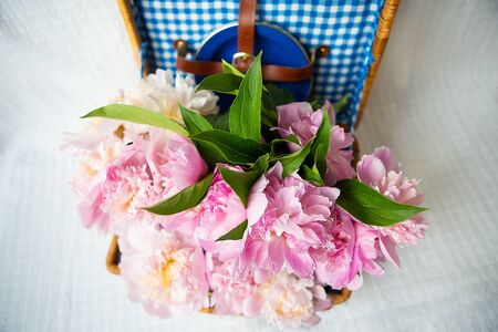 The beauty of a pink peonies bouquet in a vintage authentic brown suitcase, close-up.