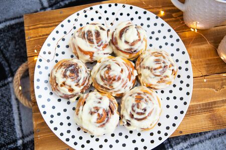 Two cups of black tea stand on a wooden tray on the sofa with a black and white checkered plaid. Fresh and fragrant cinnamon rolls close-up lie on a plate with polka dots. The garland is blinking.
