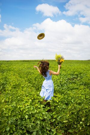 beautiful girl stands in the field with a bouquet of yellow flowers and throws her hat to the sky. Фото со стока