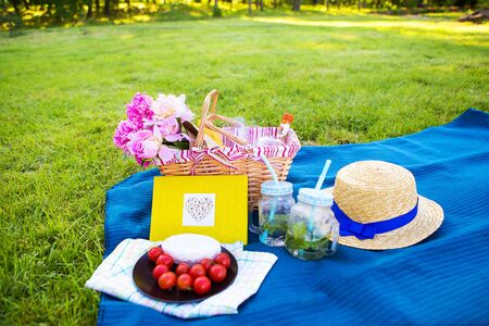 A summer picnic - a basket with beautiful flowers, a straw hat and a yellow book on a plaid