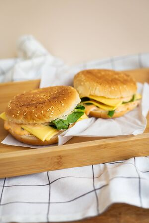 Two hamburgers are lying on a wooden tray with a white napkin, close-up