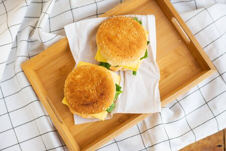 Two hamburgers lie on a wooden tray with a white napkin, close-up, top view
