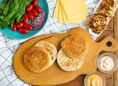 Preparation of all the ingredients for the preparation of a delicious bun burger, cutlet, cheese, salad, tomato, sauces
