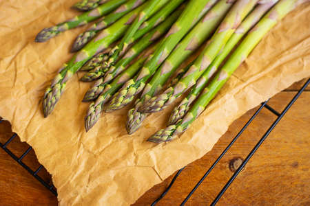Fresh green asparagus spears wrapped in brown craft paper wrapper for healthy vegetarian cuisine lying on a wooden surface, top view. Close-up