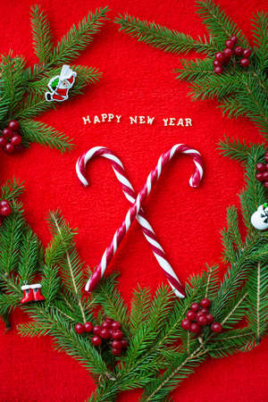 Christmas tree and candy on a red background with the words Happy New Year. Closeup